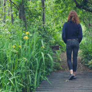 Woman walking on path in forest.