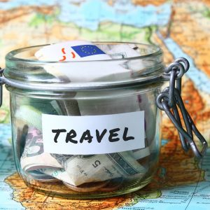 Glass jar with the word travel written on it and filled with money, on top of a world map