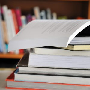 Stack of books on table in library.