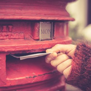 Closeup on a woman's hand as she is posting a letter