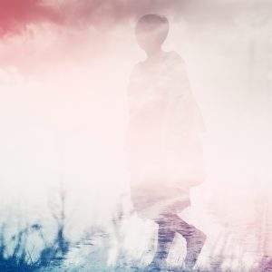 A double exposure image of a woman walking in a field, with a pink overtone.