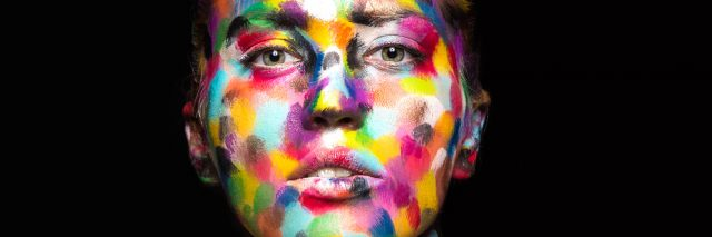 woman with her face painted in multi-colored spots