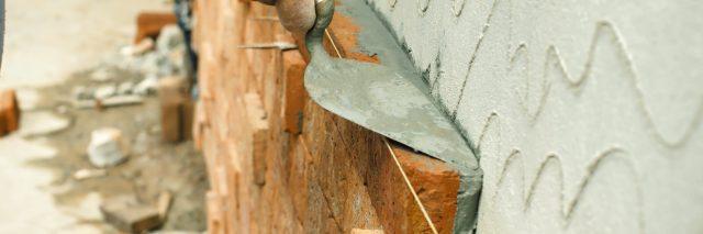 applying mortar in between bricks in a wall
