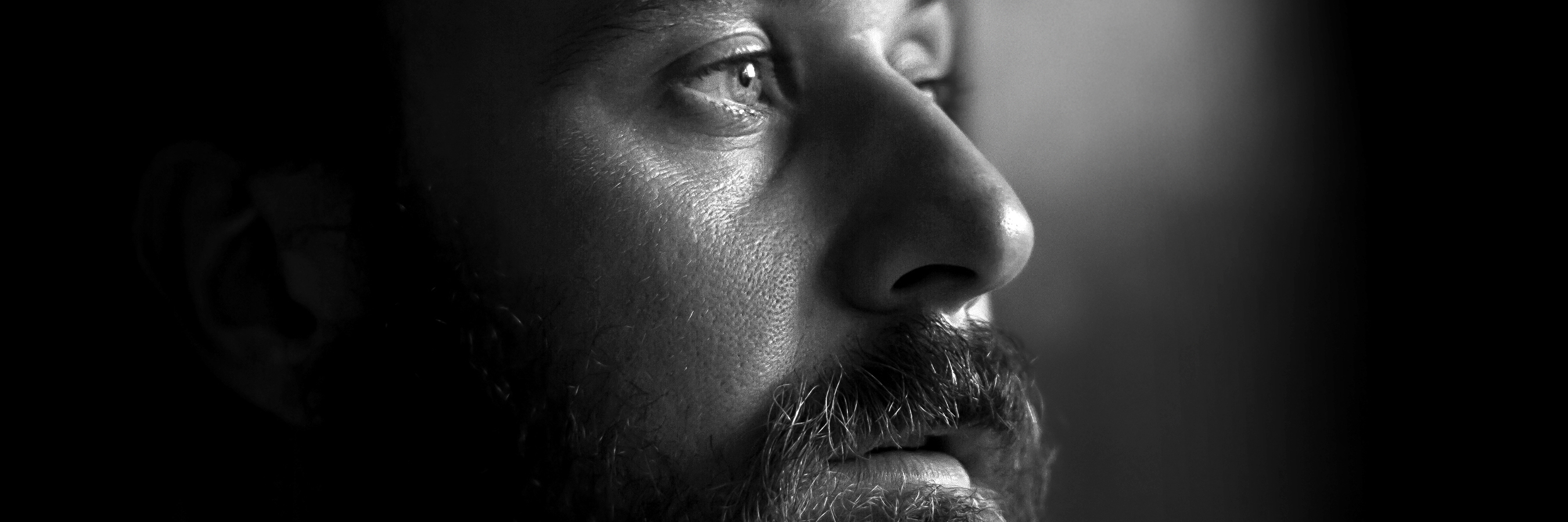 Close-up photo of a serious man with a beard in profile. Black and white image with shallow depth