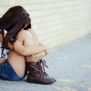 young sad girl sitting against a brick wall hugging her knees