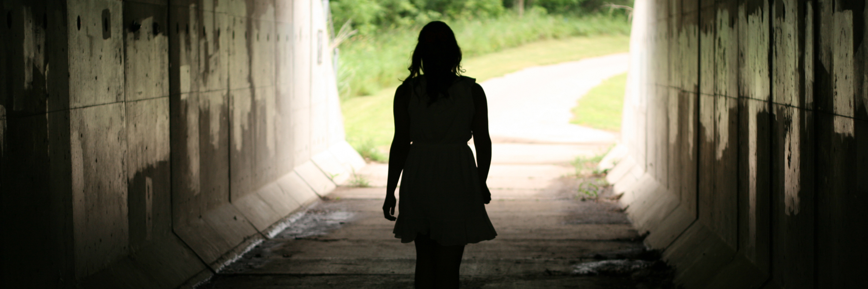 young woman walking through tunnel with light and trees at end