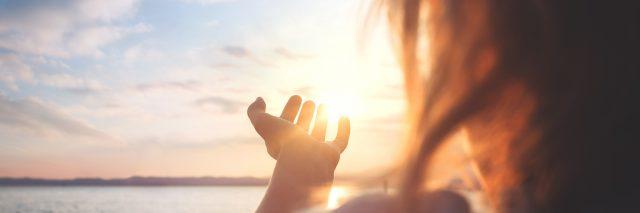 Woman reaching towards the sun.