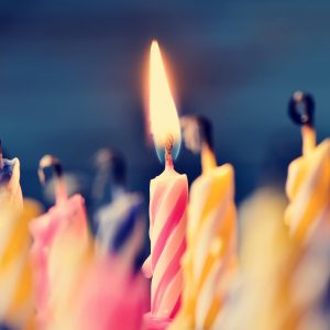 Close up on birthday cake candles, some blown out with one still lit.