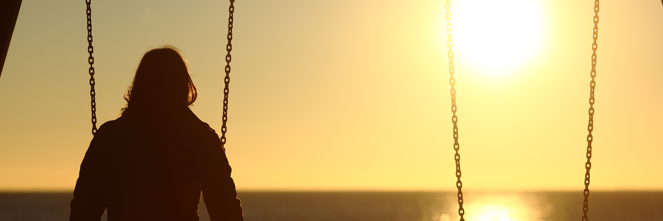 woman alone on swing watching sunset