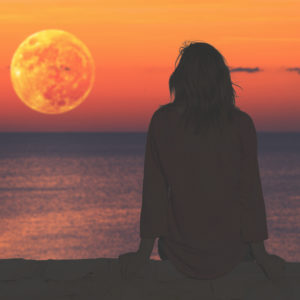 Woman watching the ocean as the moon rises.