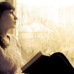 woman sitting next to a window reading a book and looking outside