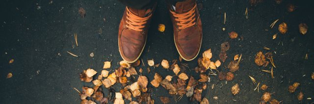 Close-up photo of two people's shoes facing each other with autumn leaves on the ground