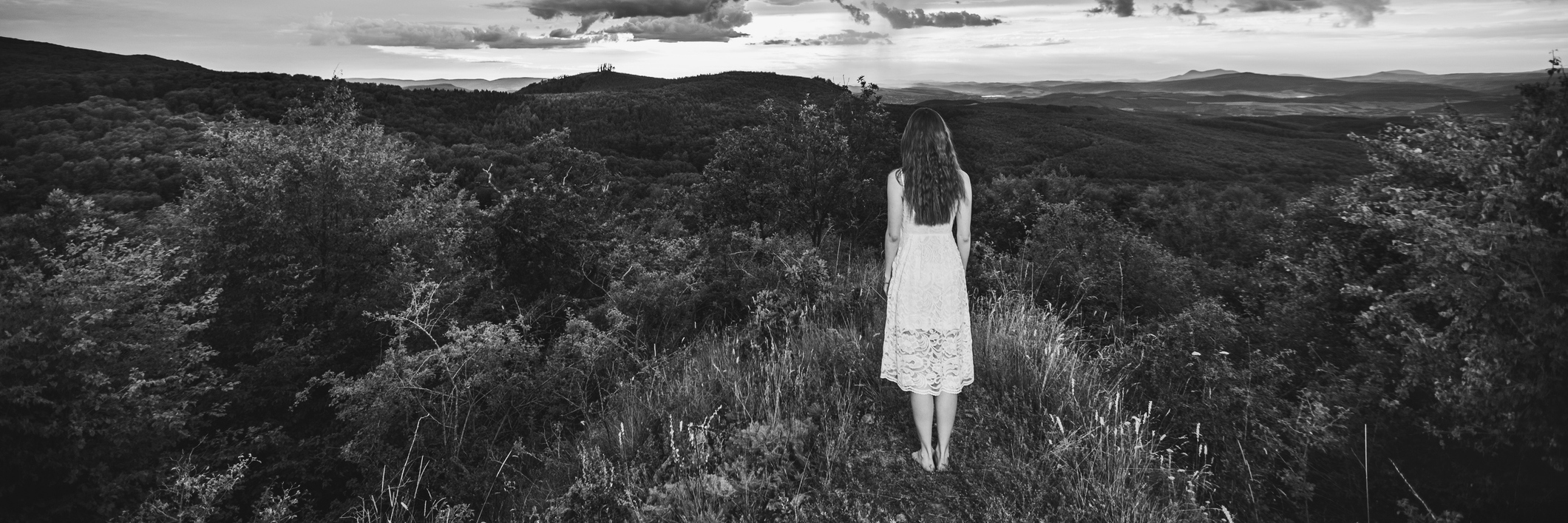 girl standing on mountain peak in black and white