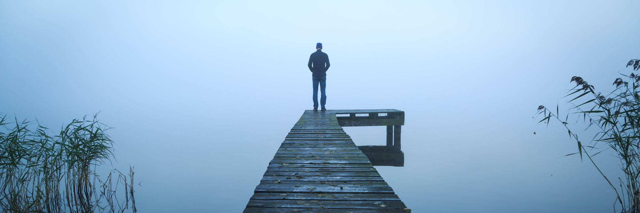 man standing alone on jetty over water on foggy day
