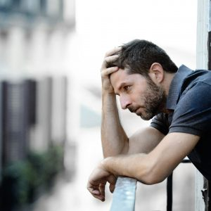 young man standing on balcony with depression