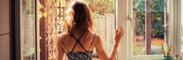 young woman standing at doorway of kitchen looking out at sunrise with arms and shoulders uncovered