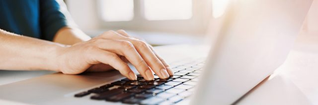 Woman's hands typing on a laptop keyboard.