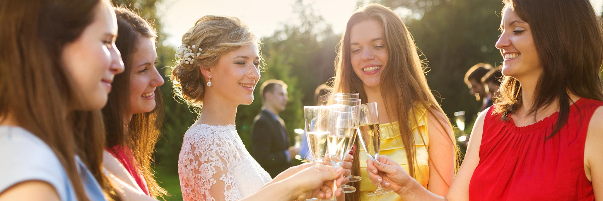 bride and bridesmaids clinking glasses at a wedding reception
