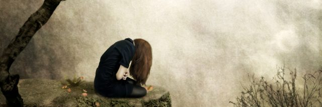 Lonely girl sitting on a rock in sorrow