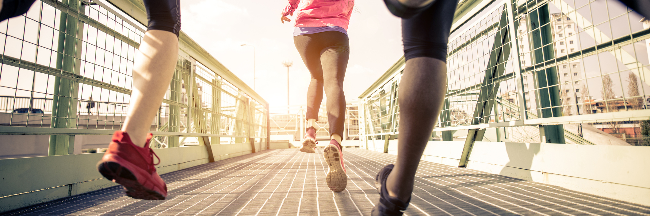three runners sprinting outdoors along bridge