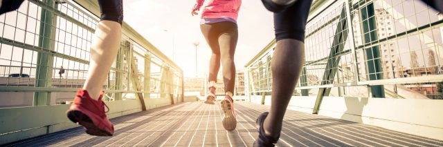 three runners sprinting outdoors along bridge