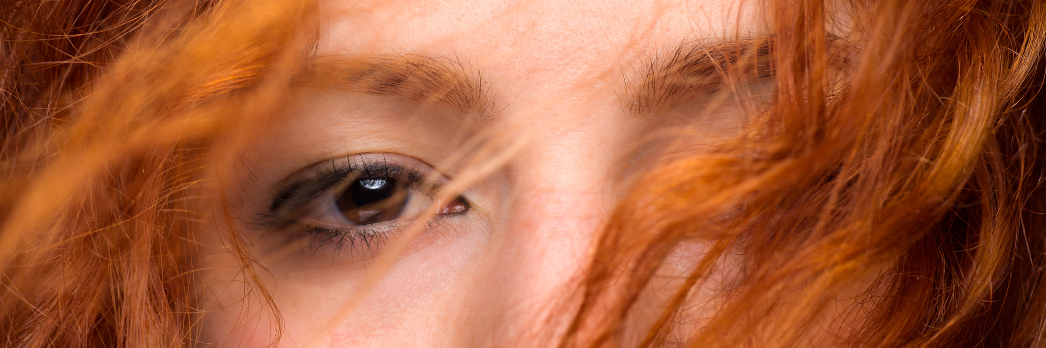 A close-up on a red-headed woman's eyes.