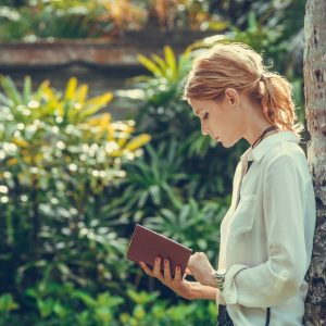A woman reading a book outside
