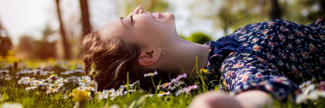 young girl lying on grass with daisies, smiling