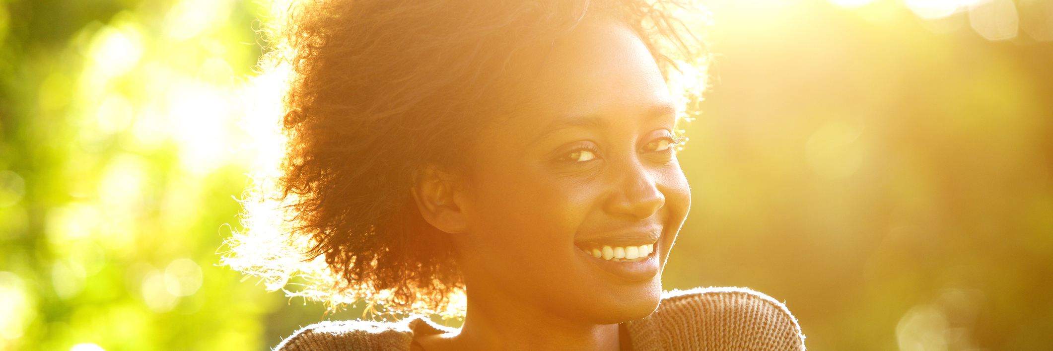Smiling Black woman at sunset.