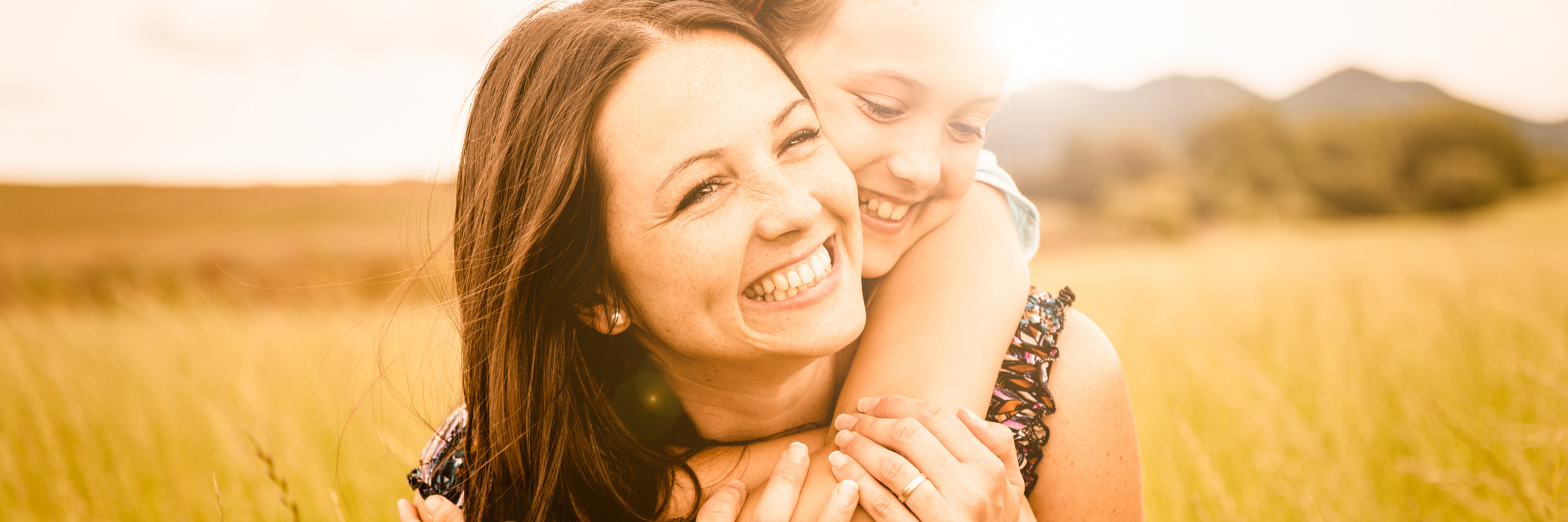 mother and daughter hugging in field smiling