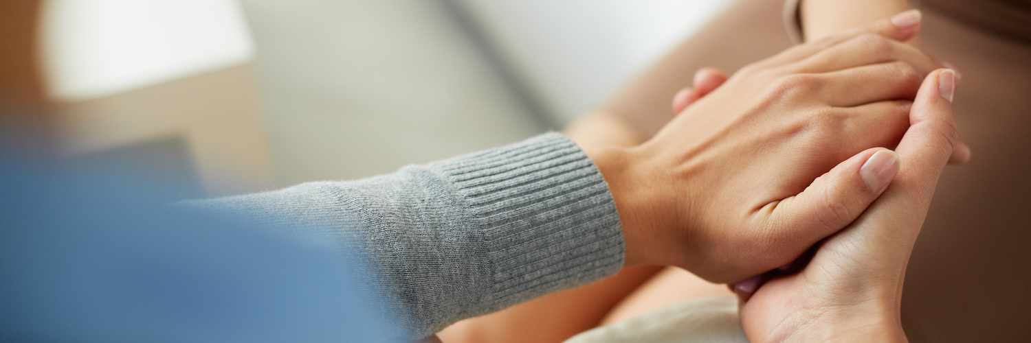 Close-up of person holding another person's hands in compassionate, comforting gesture