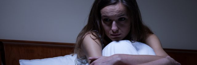 woman sitting in bed at night