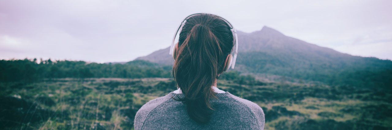 Woman in headphones listening to music while looking at a mountain.