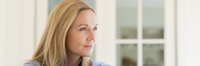 woman sitting by window thinking