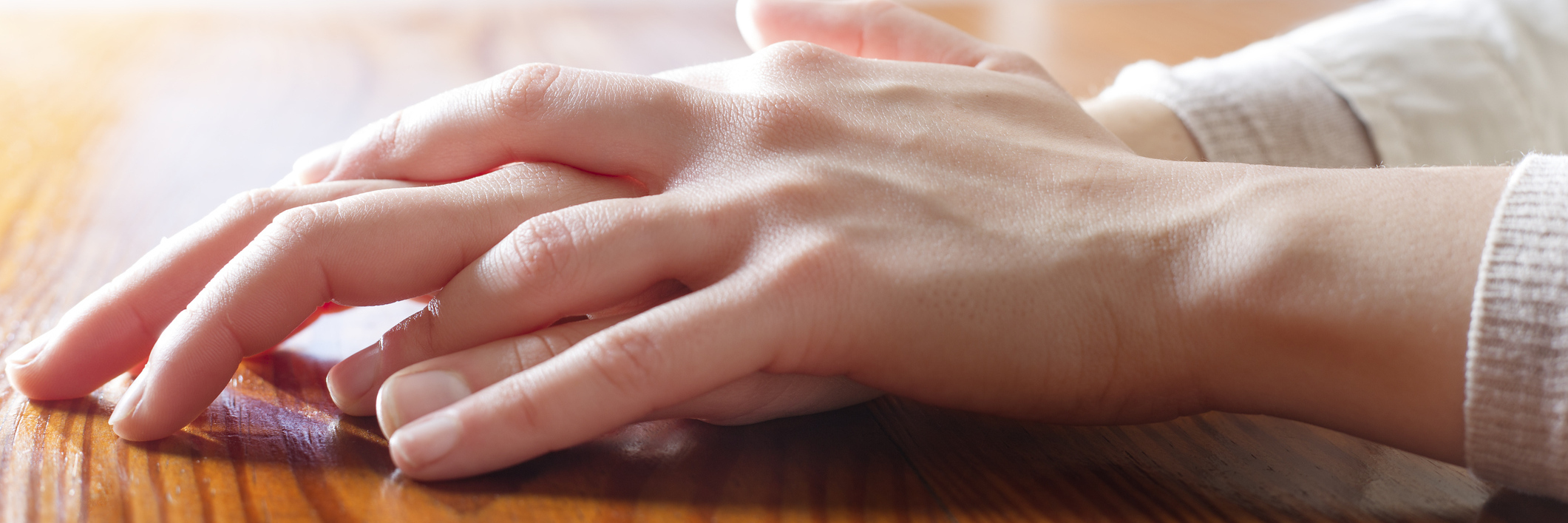 woman's hands on wooden table