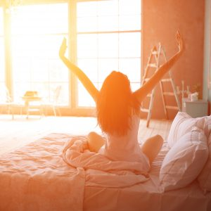 woman stretching in morning light while sitting up in bed