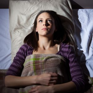 young woman lying in bed unable to sleep lost in thought