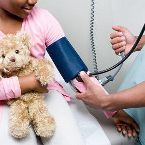 Doctor checking girl in children's hospital.