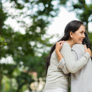 two asian women hugging in front of trees out of focus