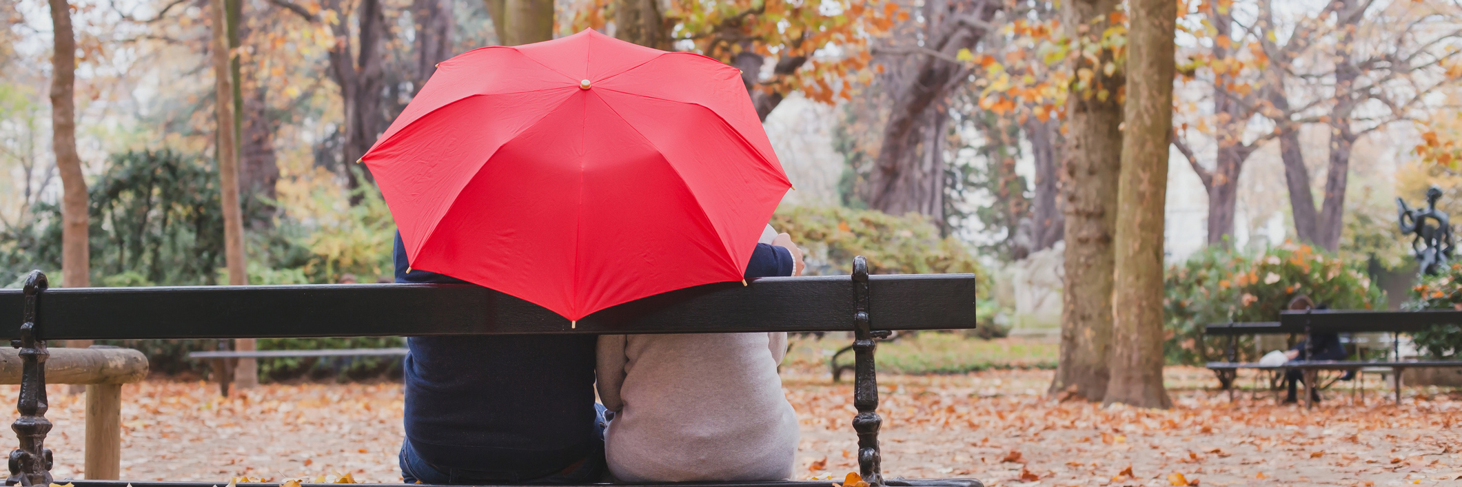 couple sitting on a park bench under a red umbrella