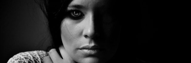 Black and white image of a woman looking seriously into camera.