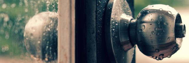 Rain drops on door handle and glass window on rainy day