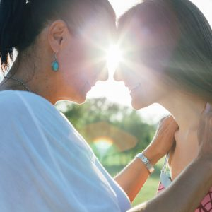 teen daughter with mature mother hugging in nature at sunset