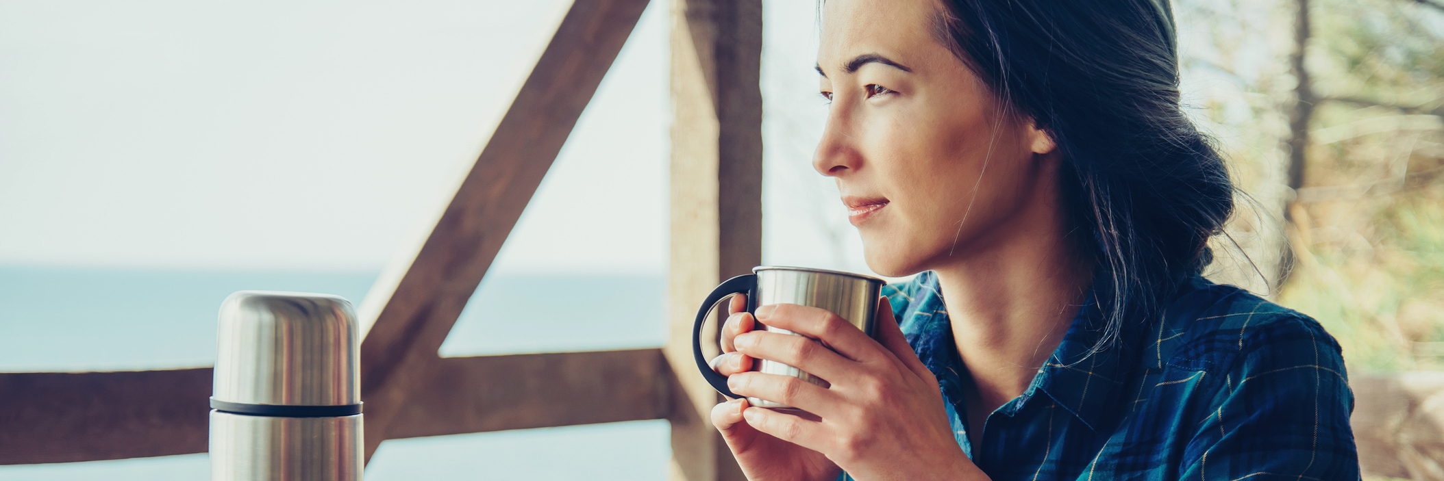 young woman sitting on wooden porch drinking coffee from thermos