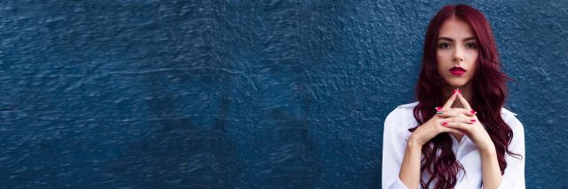 A serious woman stands in front of a blue wall.