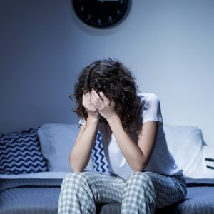 young woman sitting on bed with face buried in hands depression