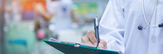 doctor writing prescription on clipboard