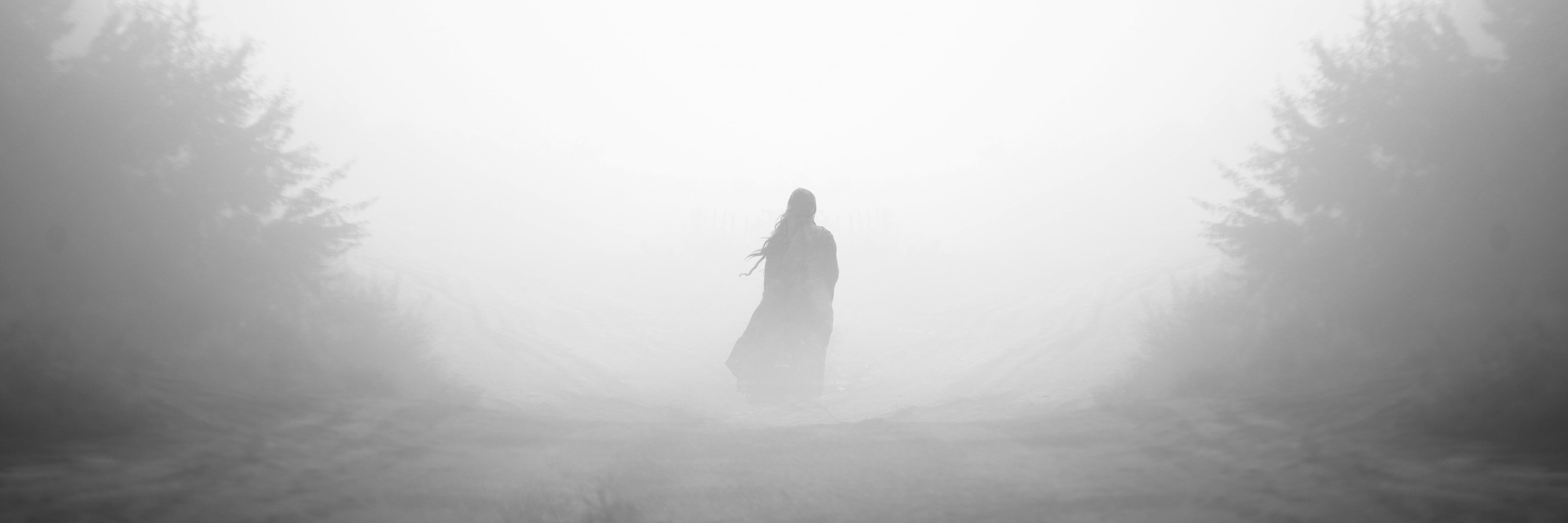 woman walking down a foggy road in the forest