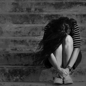 black and white photo of a woman sitting on a staircase with her head down crying