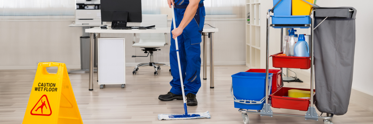 Male janitor mopping floor in office.